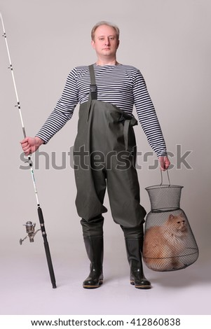 Fisherman in waders, holding a fishing equipment and cat at  grid. - stock photo