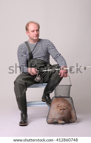 Fisherman in waders sitting on chair, holding a fishing equipment with cat - stock photo
