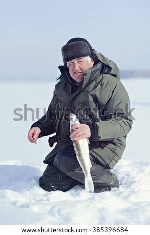 Fisherman in winter on the ice caught fish. A fisherman holds a fish in his hands. - stock photo