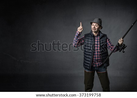 fisherman indicated empty space, dark background - stock photo