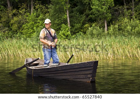 Fisherman is standing in the old, wooden rowboat and catching the fish on sunny day.