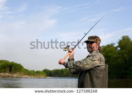 Fisherman makes casting tackle in the river. - stock photo
