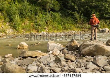 Fisherman on a mountain river catch exotic fish. Trout fishing in the Carpathian rivers. Untouched nature of the mountains. Photo for fishing and Natural magazines, posters and websites. - stock photo