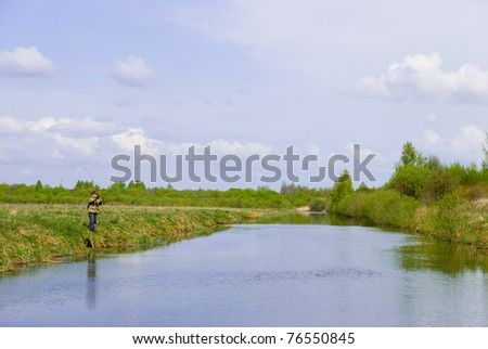 Fisherman on a river. - stock photo