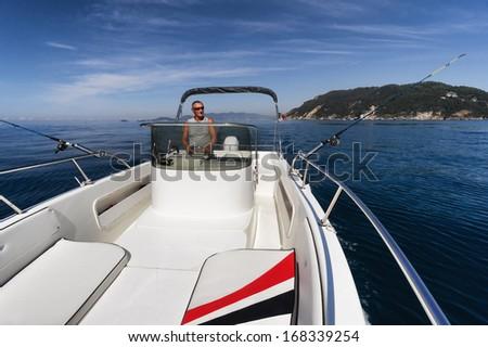fisherman on boat fishing along coast - stock photo