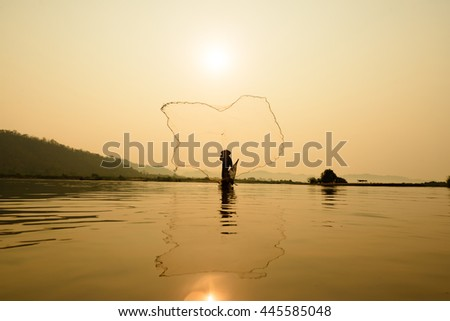 fisherman on boat with sunrise background, the Mekong River in Thailand - stock photo