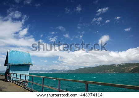 Fisherman on the old jetty at Petone to the Pacific ocean harbor against a background of blue sky, Wellington,New Zealand. - stock photo