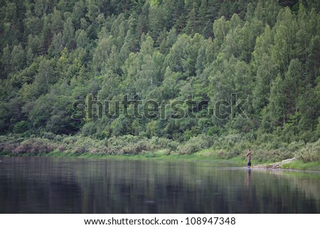 fisherman on the river bank near the forest - stock photo