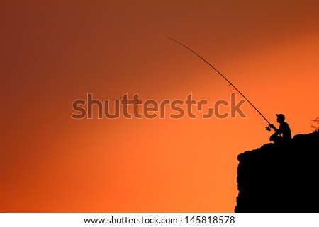fisherman on the rocks - stock photo