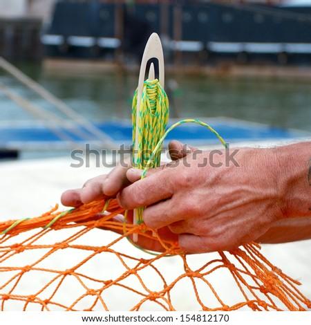 Fisherman repairing his net - stock photo