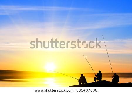 Fisherman's fishing on a beach  before sunset - stock photo