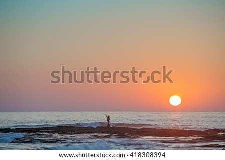 Fisherman's silhouette on seashore at sunset