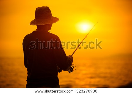 Fisherman silhouette at sunset near the sea with a fishing rod