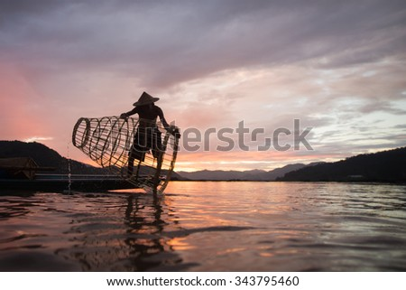 fisherman silhouette in mekhong river thailand - stock photo