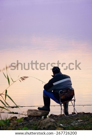 fisherman sitting at sunset and fishing  - stock photo