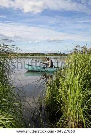 Fisherman sitting in the boat with fishing rod in his hands - stock photo