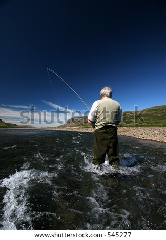 Fisherman standing in river with a fish on the line - stock photo