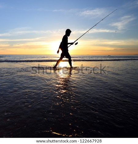 Fisherman standing on a pier at evening sky background in the sea water - stock photo
