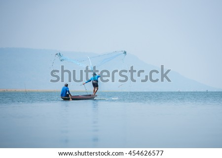 Fisherman throwing fish net to catch the fishes in the lake