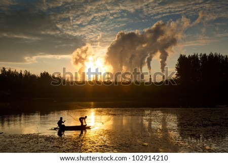 Fisherman throwing net and hot steam from big chimney background. - stock photo