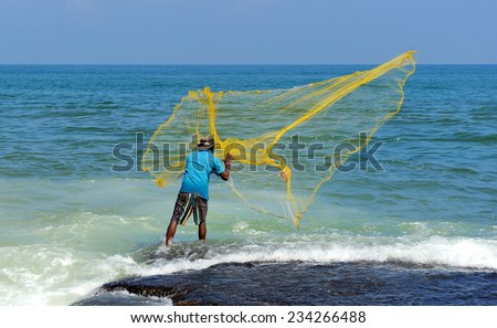 Fisherman throwing yellow fishing net - stock photo