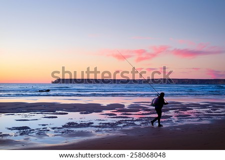 Fisherman walking on the ocean beach at sunset. Portugal - stock photo