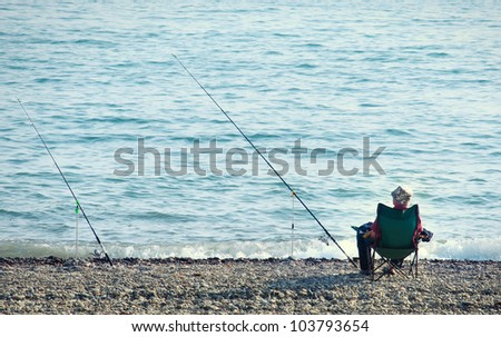 fisherman with a fishing rod fishing on the background of the sea - stock photo