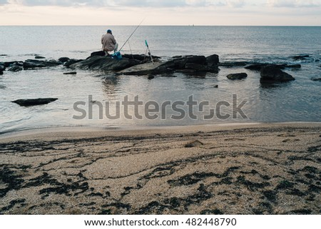 fisherman with a fishing rod on the beach at dawn rays