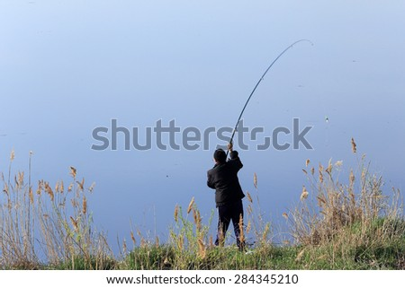 fisherman with a fishing rod on the shore of a calm river on a spring morning - stock photo