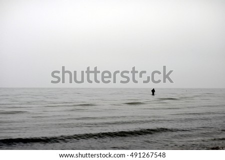 fisherman with a rod in the sea at a northern beach
