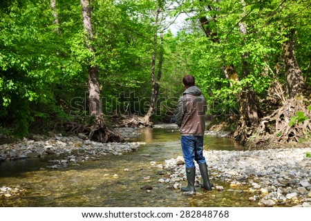 Fisherman with fly-fishing on mountain river. Spring time