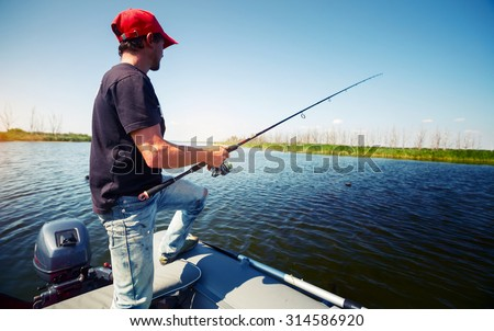 Fisherman with rod in the boat on the pond at sunny day