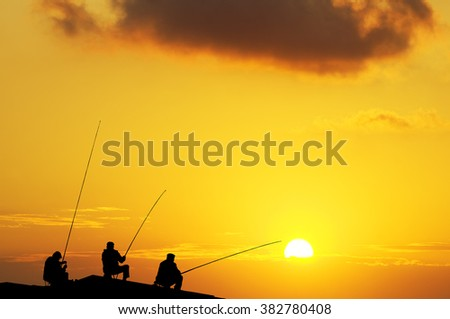 Fishermans fishing on a beach  before sunset - stock photo