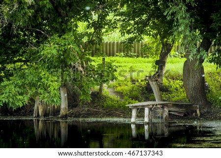 fishermans place in a village on the lake among the green summer in the dark water