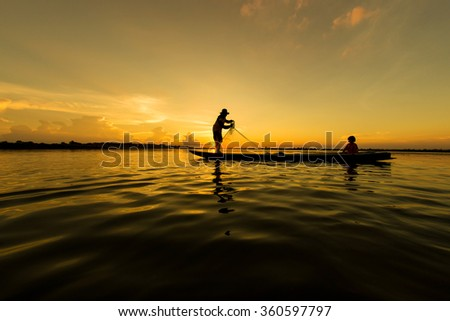 Fishermen and children fishing in the river a golden color silhouette, Thailand.