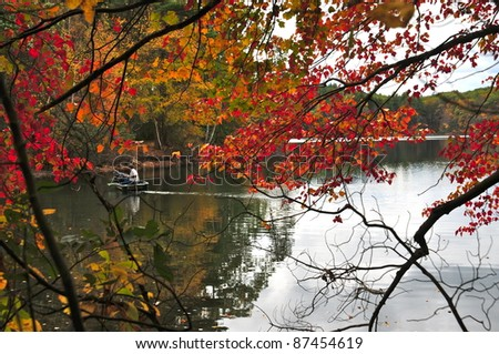 Fishermen are out in their boat amidst the beauty of Walden Ponds - stock photo