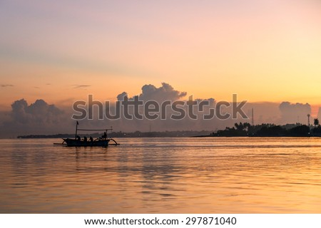 Fishermen boats going into the ocean during sunrise time near Lovina beach in Bali, Indonesia. Horizontal colorful photo. - stock photo