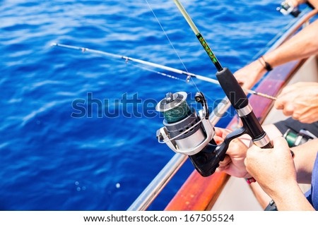 Fishermen fishing from boat in sea - stock photo