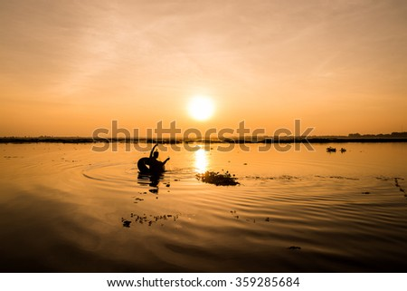 Fishermen fishing in a lake at sunset . Suggests the stripe water waves reflect the beautiful sunshine .