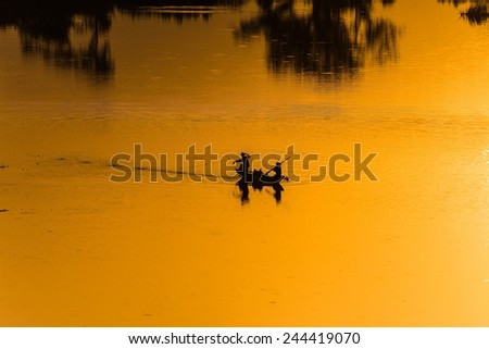 fishermen fishing on a lake in Sri Lanka while the setting sun illuminates their fishing grounds - stock photo