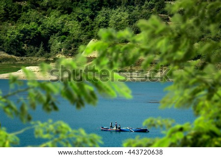 fishermen fishing on lake with small boats - stock photo