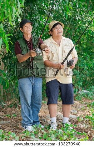 Fishermen in wait standing in the forest - stock photo