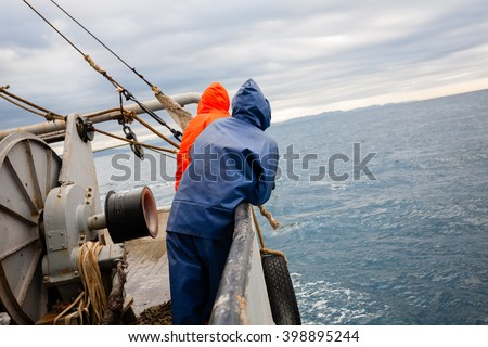 Fishermen in waterproof suits on the deck of the fishing vessel. Morning time.