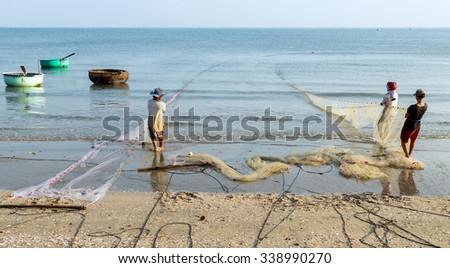 fishermen is pulled fishes in the fishing net on Mui Ne beach in Vietnam - stock photo