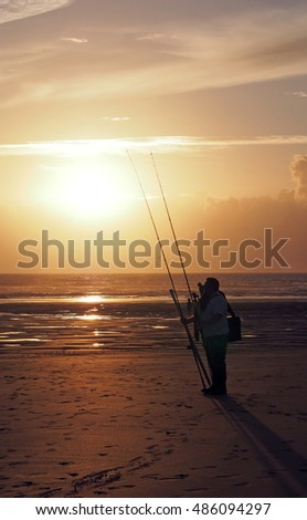 Fishermen on a beach at sunset