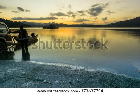 Fishermen on a boat on Lake Inle Lake, silhouette old tree reflecting in the water of the lake during colorful sunset. - stock photo