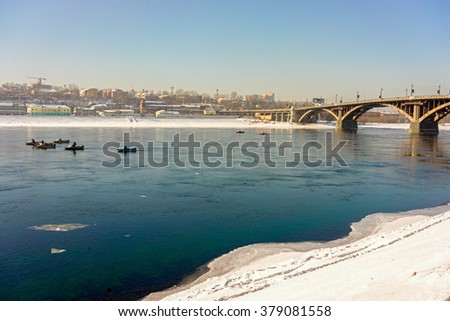 Fishermen on a boat sails near the bridge over Angara river in Irkutsk, Siberia, Russia on a winter day.