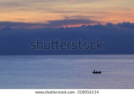 fishermen on the boat in the sea before the dawn sky background