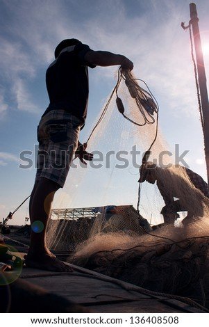 Fishermen removing fish from fishing nets at beaches HAILY, NAMDINH, VIETNAM AUGUST 28, 2011. Fishing is a traditional craft in Vietnam