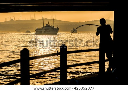 Fishermen silhouette under Galata bridge with ship on the Golden Horn, Istanbul, Turkey.